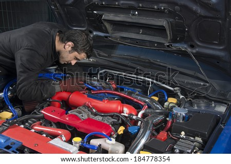 Car repairman examining modified rally car - stock photo