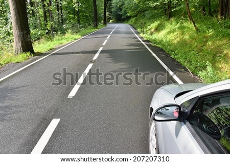 Car ride on road in sunny weather. Road in the countryside with trees - stock photo