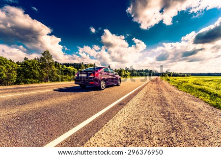 Car rides on a rural road that runs through the fields and forests. Image in the orange-blue toning - stock photo
