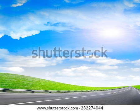 car route amongst green hills on background shining sky - stock photo