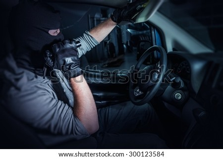 Car Rubber in Action. Grand Theft Auto. Men in Mask Looking For the Car Keys - stock photo