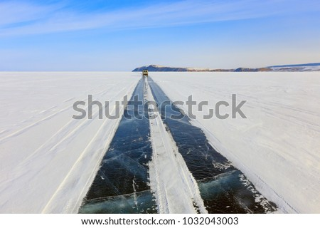 Car run on the ice road over Baikal lake in winter near Olkhon island, Irkutsk, Siberia, Russia.