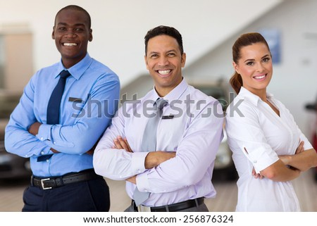 car sales staff standing inside showroom - stock photo