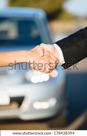 Car sales. Two people shaking hands after commercial business agreement. - stock photo