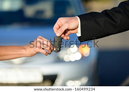Car salesman giving key to female buyer. Vehicle sales or rental concept. - stock photo