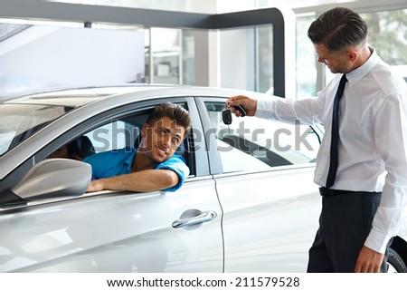 Car Salesman Handing over new Car Key to Customer at Showroom - stock photo