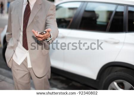 Car salesman handing over the keys - stock photo