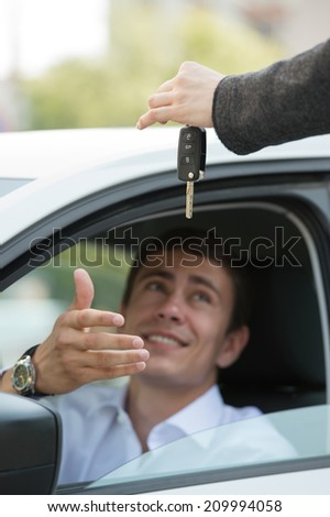 Car salesman handing over the keys for a new car to a young businessman - stock photo