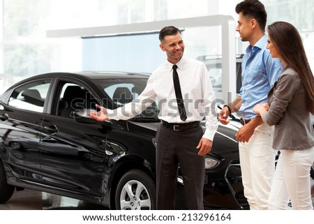 Car Salesman Invites Customers at Showroom.  - stock photo