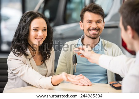 Car salesman is giving the key of the new car to the young attractive owners. - stock photo