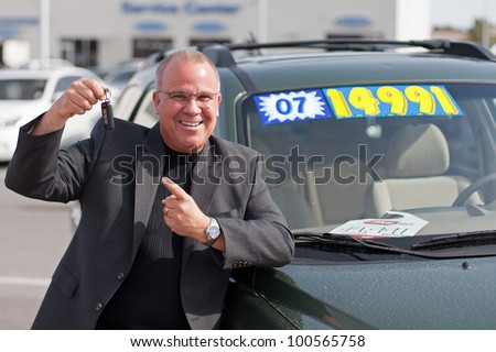 car salesman on lot with price sticker on cae selling - stock photo