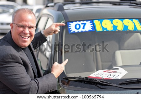 car salesman on lot with price sticker on cae selling