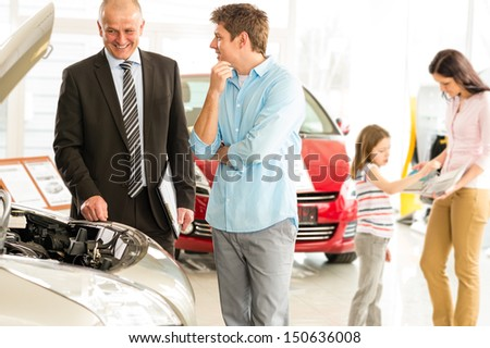 Car salesman showing the engine of the car - stock photo