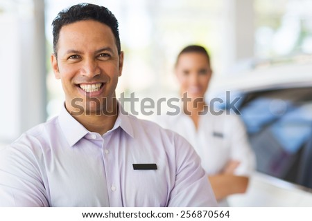 car salesman standing in front of colleague in showroom - stock photo
