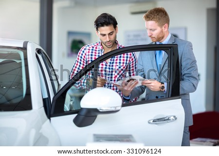 Car salesperson demonstrating a new automobile to young man - stock photo