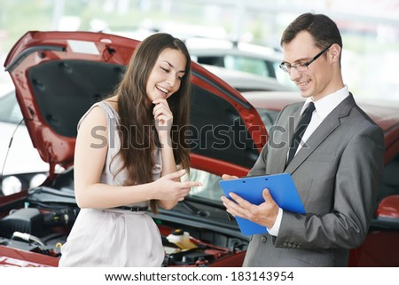 Car salesperson demonstrating new automobile to young woman - stock photo
