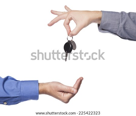 Car seller just about to drop the keys to the buyers hand.