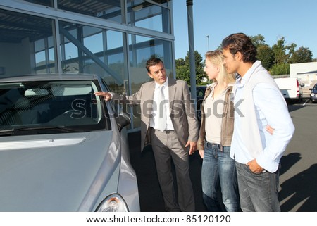 Car seller showing vehicle to couple of purchasers - stock photo