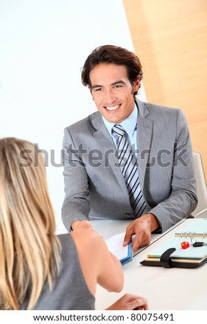 Car seller with buyer in office - stock photo