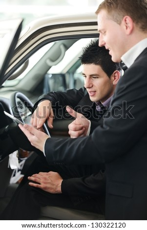 Car seller with car buyer looking at digital tablet - stock photo