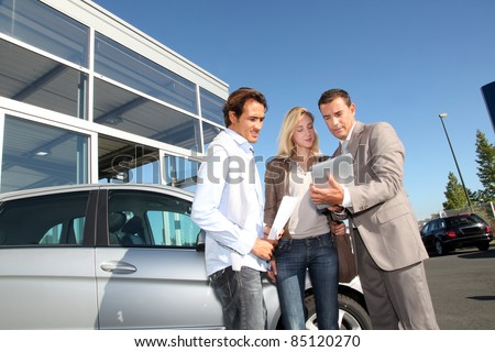 Car seller with couple looking at electronic tablet - stock photo