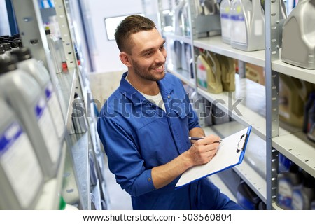 car service, repair, maintenance and people concept - smiling auto mechanic man or smith writing to clipboard at workshop or warehouse
