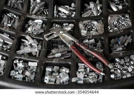 Car service. The tool for repair - Lead small weights and pincers for Wheel Balancing. - stock photo