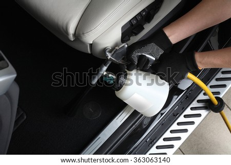 Car service. Worker washing of  interior by a special cleaners under pressure. - stock photo