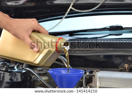 Car servicing mechanic pouring oil to engine - stock photo