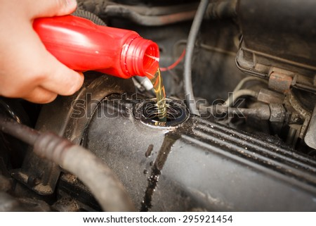 Car servicing mechanic pouring oil to engine. Closeup of fresh oil being poured into a car. - stock photo