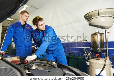 Car servicing, replacing of motor oil and filter at auto repair shop - stock photo