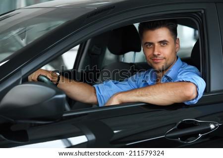 Car Showroom. Happy Man inside Car of His Dream. - stock photo
