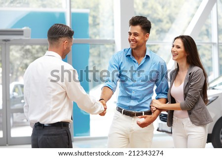 Car Showroom. Young Couple is Meeting with Seller in Auto Salon - stock photo