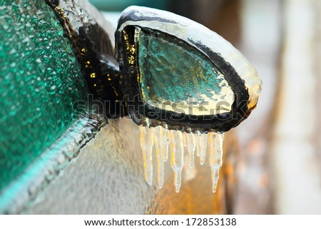 Car side mirror covered with ice and icicles, close up - stock photo