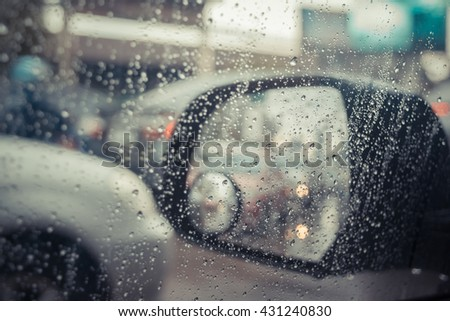 Car side mirror for rear view and rain water drops with traffic reflection background , process in vintage style - stock photo