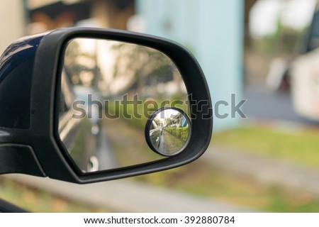 Car side mirror for rear view with traffic reflection background - stock photo