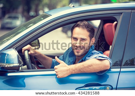 Car side window. Man driver happy smiling showing thumbs up driving sport blue car isolated outside parking lot background. Handsome young man excited about his new vehicle. Positive face expression - stock photo