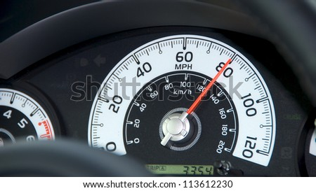 Car speedometer Close up on a car speedometer on black dashboard. - stock photo