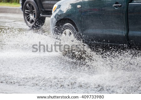 Car splashes through a large puddle on a flooded street  - stock photo