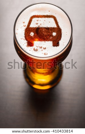 car symbol on foam in beer glass on black table, view from above