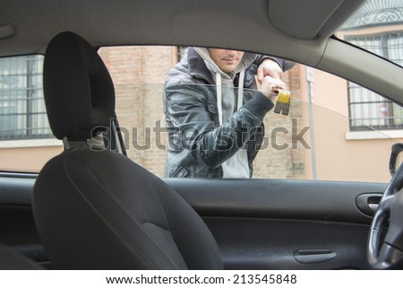 car thief breaking a window for stealing - stock photo