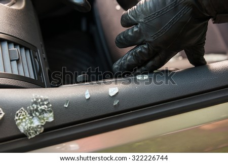 Car thief entering a parking car and going away with it. - stock photo