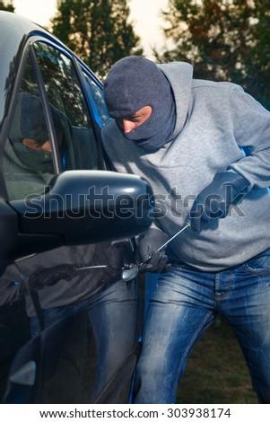 Car thief stealing a car. Breaking the lock. - stock photo