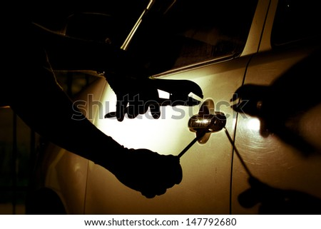 Car thief using a tool to break into a car. - stock photo