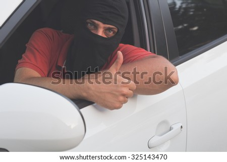 Car thief with a bloody green eyes. - stock photo
