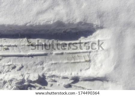 Car tire imprint in snow - stock photo