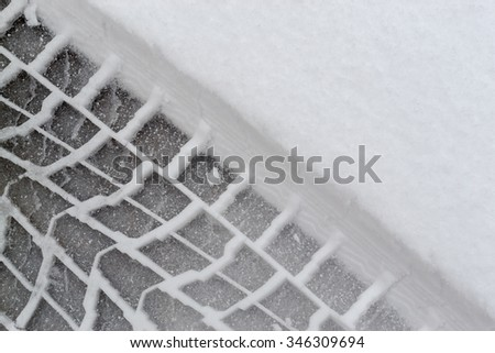 Car tire imprints dug into fresh winter snow during a snowstorm in the wintry weather months and icy chills making driving hazardous - stock photo