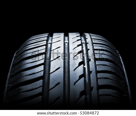 car tire on black background - stock photo