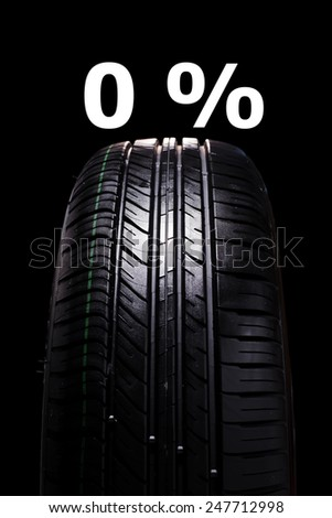 Car tire on black background with text 0% on top - stock photo
