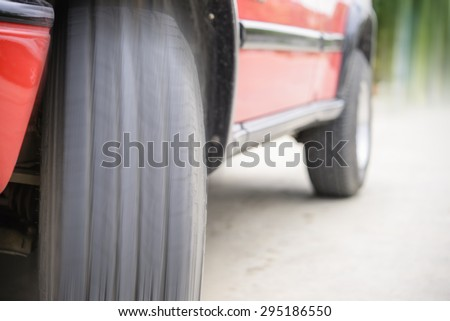 Car tire on the road ready to go with motion blur - stock photo